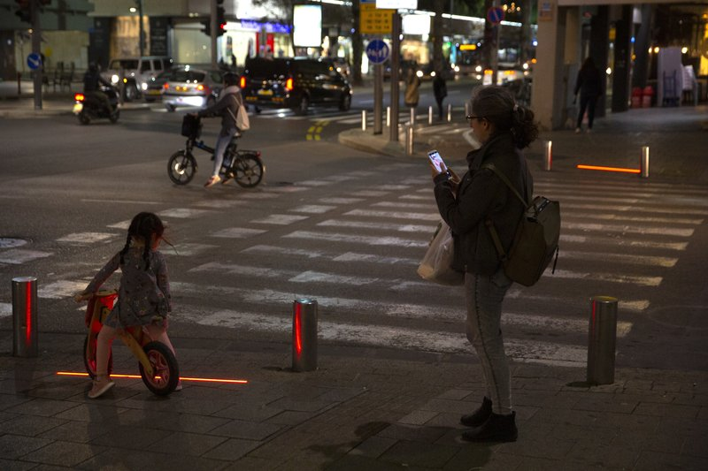 In this Wednesday, March 13, 2019 photo, Israeli pedestrians stand in front of embedded LED stoplights at a crosswalk in Tel Aviv, Israel. (AP Photo/Sebastian Scheiner)