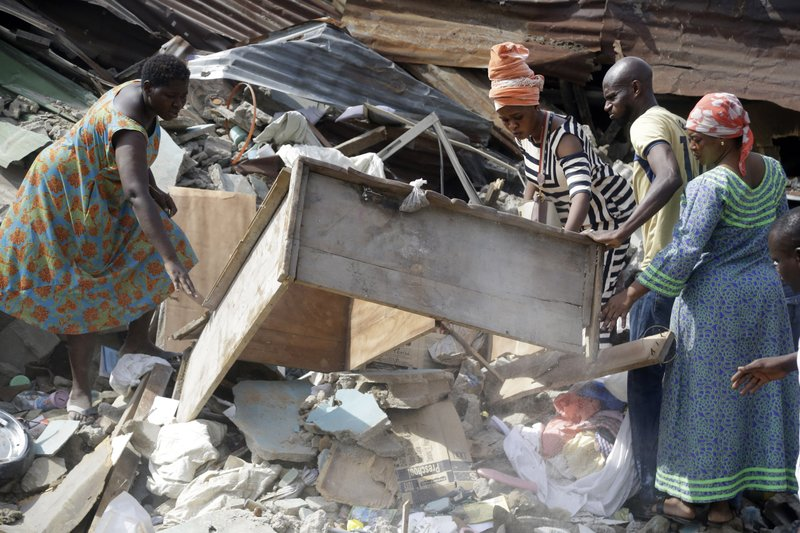 Local people attend the scene after a building collapsed in Lagos, Nigeria, Thursday March 14, 2019. Search and rescue work continues in Nigeria a day after a building containing a school collapsed with scores of children said to be inside. (AP Photo/Sunday Alamba)