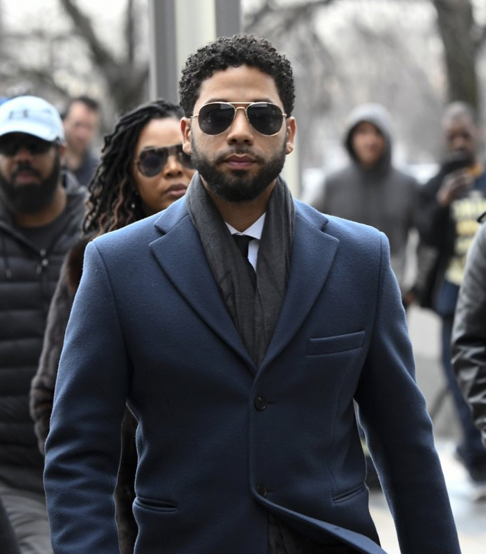 Empire actor Jussie Smollett, center, arrives at the Leighton Criminal Court Building for his hearing on Thursday, March 14, 2019, in Chicago. (AP Photo/Matt Marton)