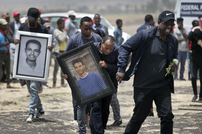Family members of the flight's main pilot, Captain Yared Getachew, carry photographs of him as they mourn at the scene where the Ethiopian Airlines Boeing 737 Max 8 crashed shortly after takeoff on Sunday killing all 157 on board, near Bishoftu, south-east of Addis Ababa, in Ethiopia Thursday, March 14, 2019. (AP Photo/Mulugeta Ayene)