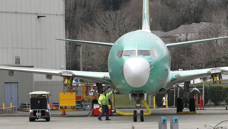 FILE- In this March 11, 2019, file photo a worker stands near a Boeing 737 MAX 8 airplane parked at Boeing Co. (AP Photo/Ted S. Warren, File)