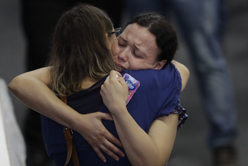Relatives embrace during a collective wake of the victims of the shooting at the Raul Brasil State School in Suzano, greater Sao Paulo area, Brazil, Thursday, March 14, 2019. (AP Photo/Andre Penner)