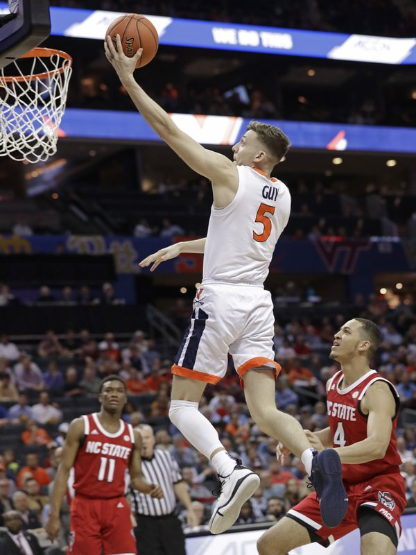 Virginia's Kyle Guy (5) drives past North Carolina State's Jericole Hellems (4) during the first half of an NCAA college basketball game in the Atlantic Coast Conference tournament in Charlotte, N. (AP Photo/Chuck Burton)
