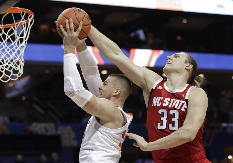 North Carolina State's Wyatt Walker, right, blocks a shot by Virginia's Jack Salt, left, during the first half of an NCAA college basketball game in the Atlantic Coast Conference tournament in Charlotte, N. (AP Photo/Chuck Burton)