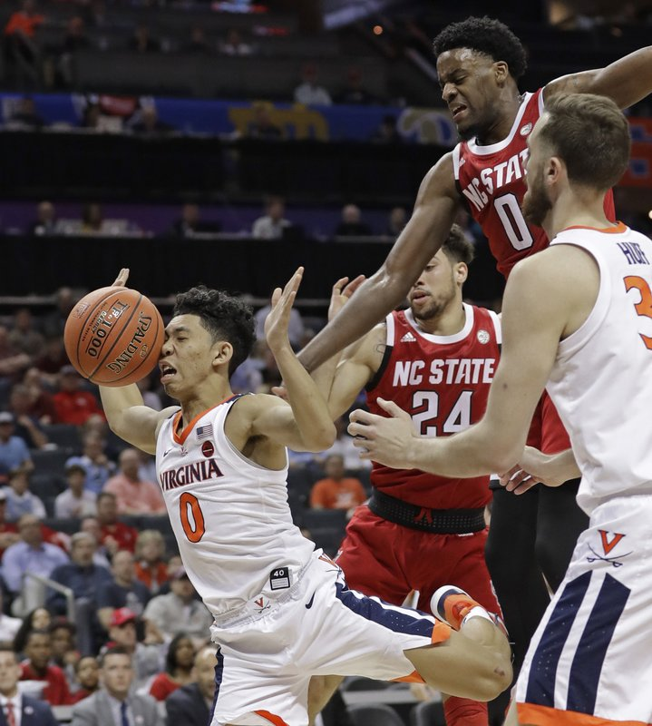 Virginia's Kihei Clark (0) loses the ball as he drives between North Carolina State's Devon Daniels (24) and DJ Funderburk, back, during the first half of an NCAA college basketball game in the Atlantic Coast Conference tournament in Charlotte, N. (AP Photo/Chuck Burton)