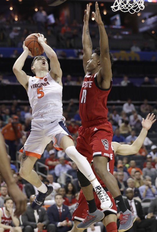 Virginia's Kyle Guy (5) shoots against North Carolina State's C.J. Bryce (13) during the first half of an NCAA college basketball game in the Atlantic Coast Conference tournament in Charlotte, N. (AP Photo/Chuck Burton)