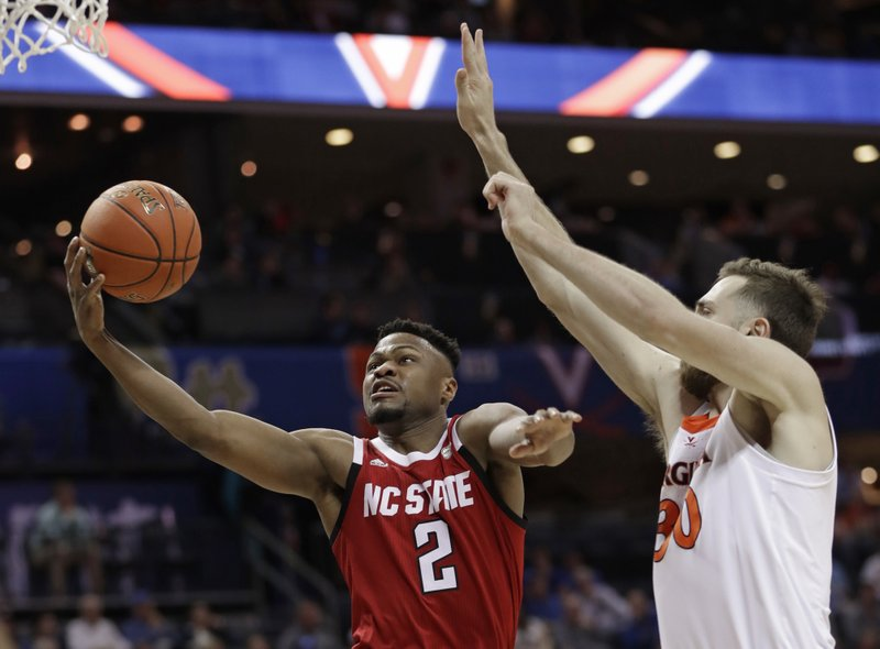 North Carolina State's Torin Dorn (2) drives against Virginia's Jay Huff (30) during the first half of an NCAA college basketball game in the Atlantic Coast Conference tournament in Charlotte, N. (AP Photo/Nell Redmond)