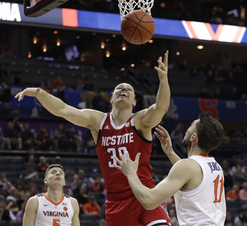 North Carolina State's Wyatt Walker (33) battles Virginia's Ty Jerome (11) for a rebound during the first half of an NCAA college basketball game in the Atlantic Coast Conference tournament in Charlotte, N. (AP Photo/Nell Redmond)