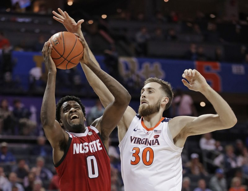 North Carolina State's DJ Funderburk (0) shoots against Virginia's Jay Huff (30) during the first half of an NCAA college basketball game in the Atlantic Coast Conference tournament in Charlotte, N. (AP Photo/Nell Redmond)