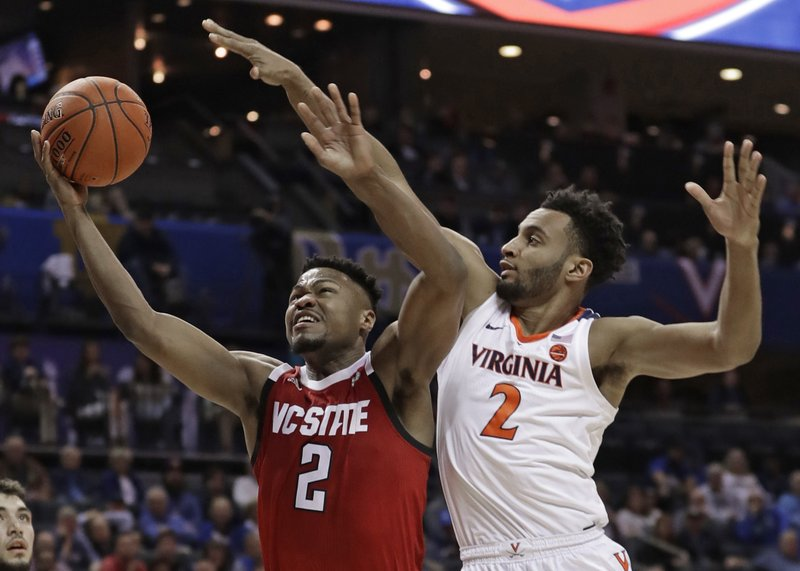 North Carolina State's Torin Dorn, left, drives against Virginia's Braxton Key, right, during the first half of an NCAA college basketball game in the Atlantic Coast Conference tournament in Charlotte, N. (AP Photo/Nell Redmond)