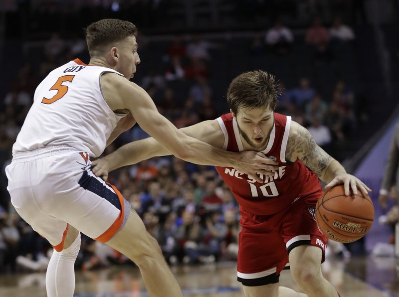 North Carolina State's Braxton Beverly (10) drives against Virginia's Kyle Guy (5) during the first half of an NCAA college basketball game in the Atlantic Coast Conference tournament in Charlotte, N. (AP Photo/Nell Redmond)