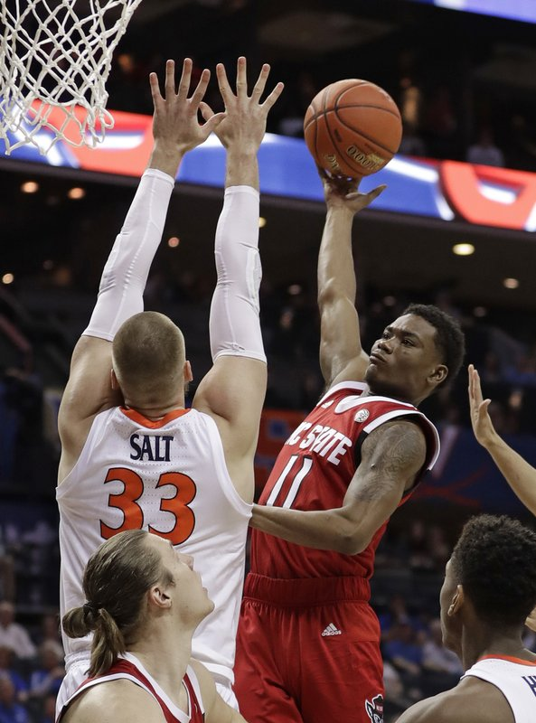 North Carolina State's Markell Johnson (11) shoots against Virginia's Jack Salt (33) during the first half of an NCAA college basketball game in the Atlantic Coast Conference tournament in Charlotte, N. (AP Photo/Nell Redmond)