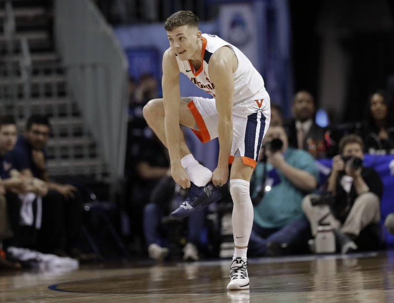 Virginia's Kyle Guy (5) puts on his shoe after losing it during the first half of an NCAA college basketball game against North Carolina State in the Atlantic Coast Conference tournament in Charlotte, N. (AP Photo/Chuck Burton)