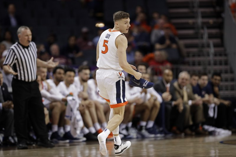 Virginia's Kyle Guy (5) holds his shoe as he runs down the court during the first half of an NCAA college basketball game against North Carolina State in the Atlantic Coast Conference tournament in Charlotte, N. (AP Photo/Chuck Burton)