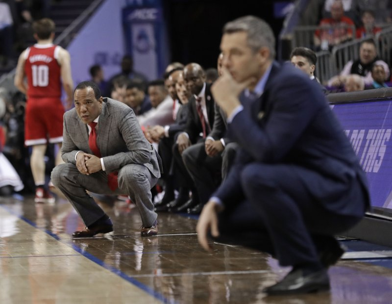North Carolina State head coach Kevin Keatts, left, and Virginia head coach Tony Bennett, right, watch their teams play during the first half of an NCAA college basketball game in the Atlantic Coast Conference tournament in Charlotte, N. (AP Photo/Nell Redmond)