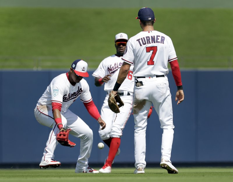Washington Nationals left fielder Juan Soto, left, watches along with teammates Victor Robles and Trea Turner (7) as a ball hit by Houston Astros' Nick Tanielu drops in for a double during the second inning of an exhibition spring training baseball game Sunday, March 3, 2019, in West Palm Beach, Fla. (AP Photo/Jeff Roberson)