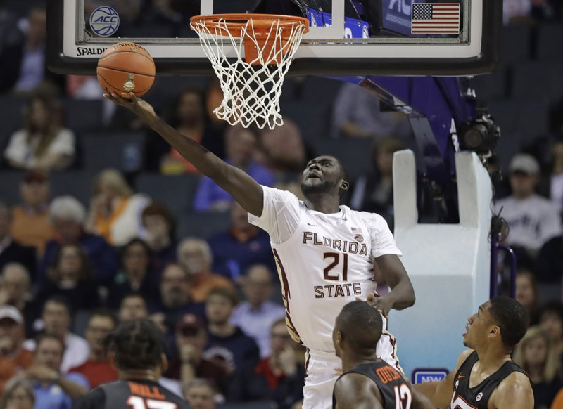 Florida State's Christ Koumadje (21) drives to the basket against Virginia Tech during the first half of an NCAA college basketball game in the Atlantic Coast Conference tournament in Charlotte, N. (AP Photo/Chuck Burton)