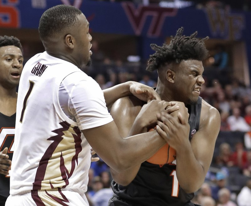 Virginia Tech's Isaiah Wilkins, right, and Florida State's Raiquan Gray, left, fight for a rebound during the first half of an NCAA college basketball game in the Atlantic Coast Conference tournament in Charlotte, N. (AP Photo/Nell Redmond)