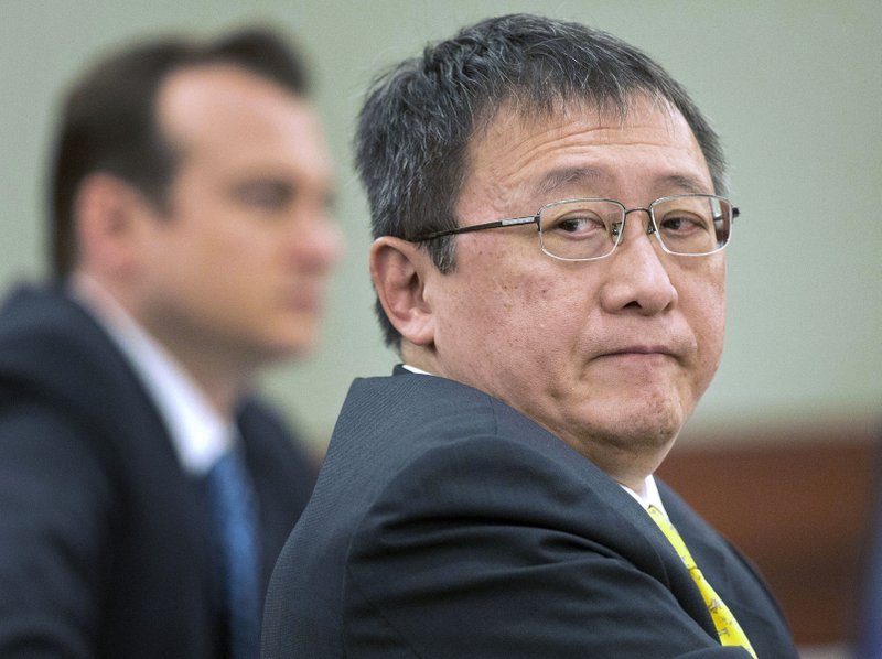 FILE - In this April 4, 2013, file photo, Hong Kong businessman Richard Suen, right, waits as counsel addresses the judge during a trial against the Las Vegas Sands Corp. (AP Photo/Julie Jacobson, File)