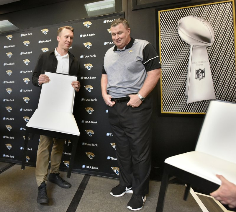 Newly signed Jacksonville Jaguars NFL football quarterback Nick Foles helps clear the interview stage for photos as he chats with head coach Doug Marrone at TIAA Bank Field in Jacksonville, Fla. (Will Dickey/The Florida Times-Union via AP)