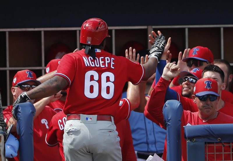 Philadelphia Phillies' Gift Ngoepe (66) celebrates at the dugout entrance after hitting a two-run home run in the seventh inning of a spring training baseball game against the Tampa Bay Rays Thursday, March 14, 2019, in Port Charlotte, Fla. (AP Photo/John Bazemore)