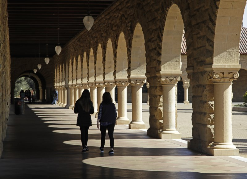 Students walk on the Stanford University campus Thursday, March 14, 2019, in Santa Clara, Calif. In the first lawsuit to come out of the college bribery scandal, several students are suing Yale, Georgetown, Stanford and other schools involved in the case, saying they and others were denied a fair shot at admission. (AP Photo/Ben Margot)
