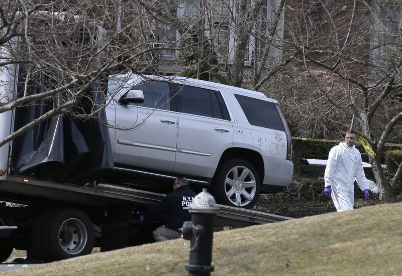 Crime scene investigators load a car that appears to have been checked for fingerprints onto a flatbed truck in the Staten Island borough of New York, Thursday, March 14, 2019. (AP Photo/Seth Wenig)