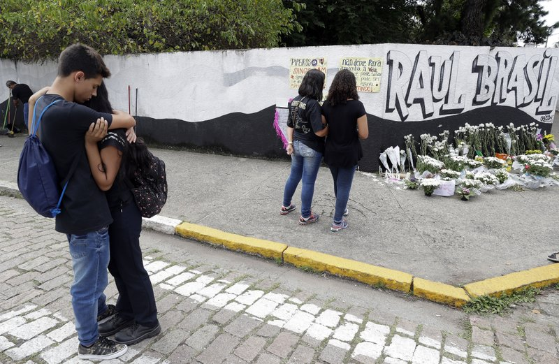 Students embrace outside the Raul Brasil state school one day after a mass shooting there in Suzano, Brazil, Thursday, March 14, 2019. (AP Photo/Andre Penner)