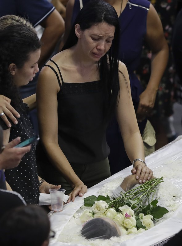 A relative mourns at the coffin containing the remains of 15-year-old Caio Oliveira, a victim of the mass shooting at the Raul Brasil State School, in Suzano, Brazil, Thursday, March 14, 2019. (AP Photo/Andre Penner)