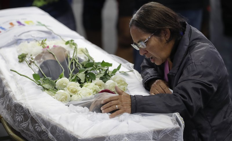 A relative mourns at the coffin containing the remains of 17-year-old Claiton Antonio Ribeiro, a victim of the mass shooting at the Raul Brasil State School, in Suzano, Brazil, Thursday, March 14, 2019. (AP Photo/Andre Penner)