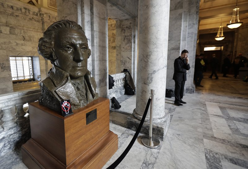 In this Tuesday, March 12, 2019 photo, a bust of George Washington looks over a hallway in the rotunda at the Capitol in Olympia, Wash. (AP Photo/Ted S. Warren)