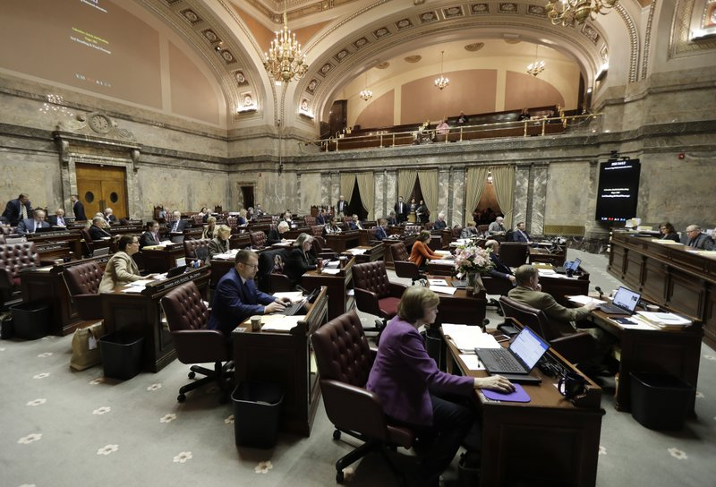In this Tuesday, March 12, 2019 photo, Washington state Senators work on the Senate floor at the Capitol in Olympia, Wash. (AP Photo/Ted S. Warren)