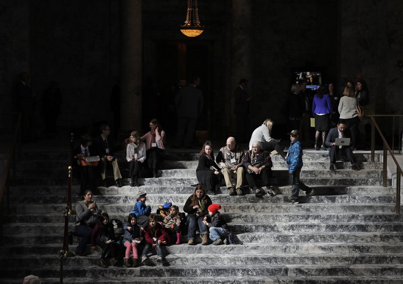 In this Tuesday, March 12, 2019 photo, visitors to the rotunda at the Capitol in Olympia, Wash. sit in noon-time light on the rotunda steps. (AP Photo/Ted S. Warren)