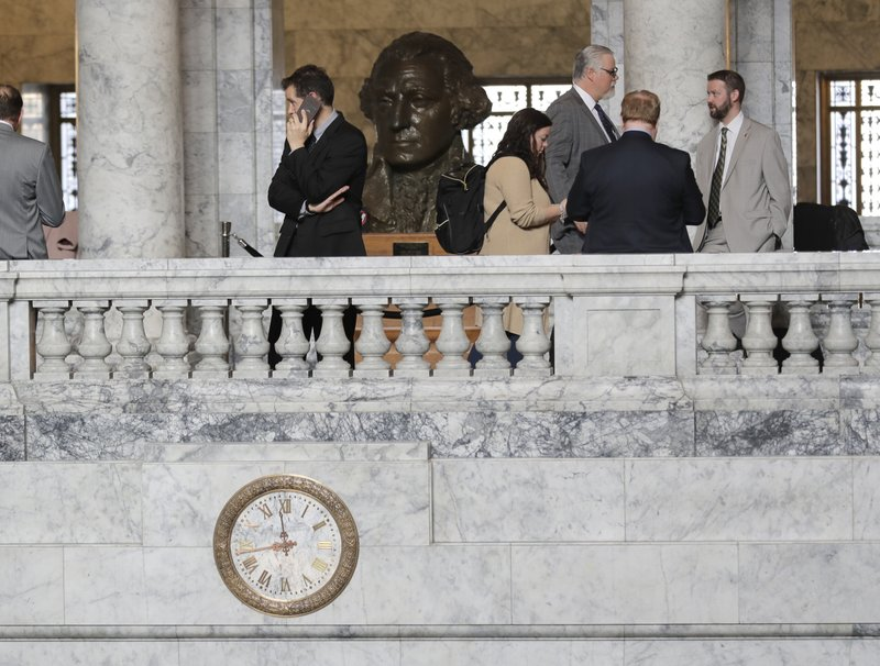 In this Tuesday, March 12, 2019 photo, a bust of George Washington looks over people gathered on a balcony hallway in the rotunda at the Capitol in Olympia, Wash. (AP Photo/Ted S. Warren)