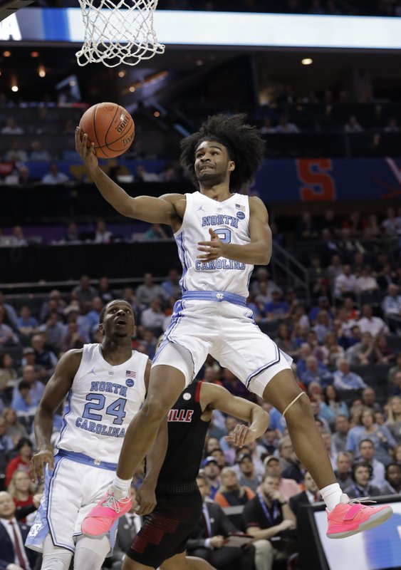North Carolina's Coby White (2) drives to the basket against Louisville during the first half of an NCAA college basketball game in the Atlantic Coast Conference tournament in Charlotte, N. (AP Photo/Chuck Burton)