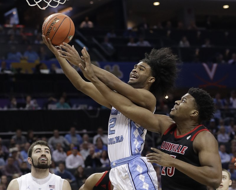 North Carolina's Coby White (2) drives past Louisville's Steven Enoch (23) during the first half of an NCAA college basketball game in the Atlantic Coast Conference tournament in Charlotte, N. (AP Photo/Chuck Burton)