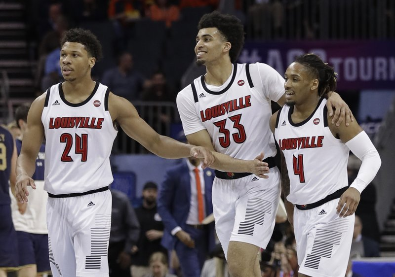 Louisville's Khwan Fore (4), Jordan Nwora (33) and Dwayne Sutton (24) celebrate in a timeout during the second half of an NCAA college basketball game in the Atlantic Coast Conference tournament in Charlotte, N. (AP Photo/Chuck Burton)
