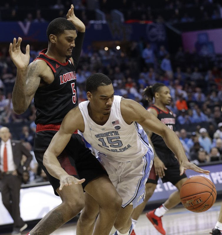 North Carolina's Garrison Brooks (15) is tripped by Louisville's Malik Williams (5) during the first half of an NCAA college basketball game in the Atlantic Coast Conference tournament in Charlotte, N. (AP Photo/Chuck Burton)