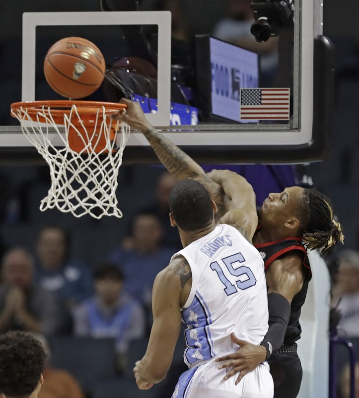 Louisville's Khwan Fore, back, is fouled by North Carolina's Garrison Brooks (15) during the first half of an NCAA college basketball game in the Atlantic Coast Conference tournament in Charlotte, N. (AP Photo/Chuck Burton)