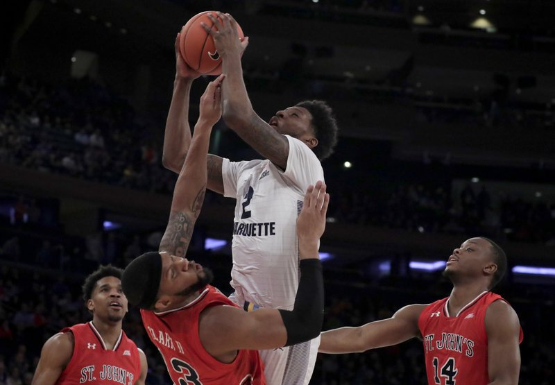 Marquette forward Sacar Anim, center, goes up for a shot against St. John's forward Marvin Clark II (13) during the first half of an NCAA college basketball game in the Big East men's tournament, Thursday, March 14, 2019, in New York. (5) and Mustapha Heron (14) look on during the play. (AP Photo/Julio Cortez)