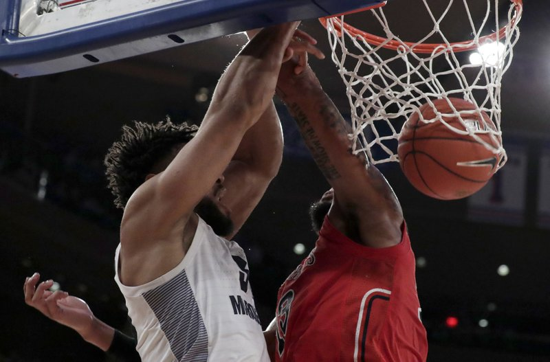 Marquette forward Ed Morrow, left, scores a basket on St. John's forward Marvin Clark II during the first half of an NCAA college basketball game in the Big East men's tournament, Thursday, March 14, 2019, in New York. (AP Photo/Julio Cortez)