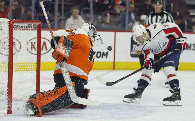 Washington Capitals' T.J. Oshie, right, shoots the puck toward Philadelphia Flyers goalie Carter Hart during the final minute of an NHL hockey game Thursday, March 14, 2019, in Philadelphia. (AP Photo/Tom Mihalek)