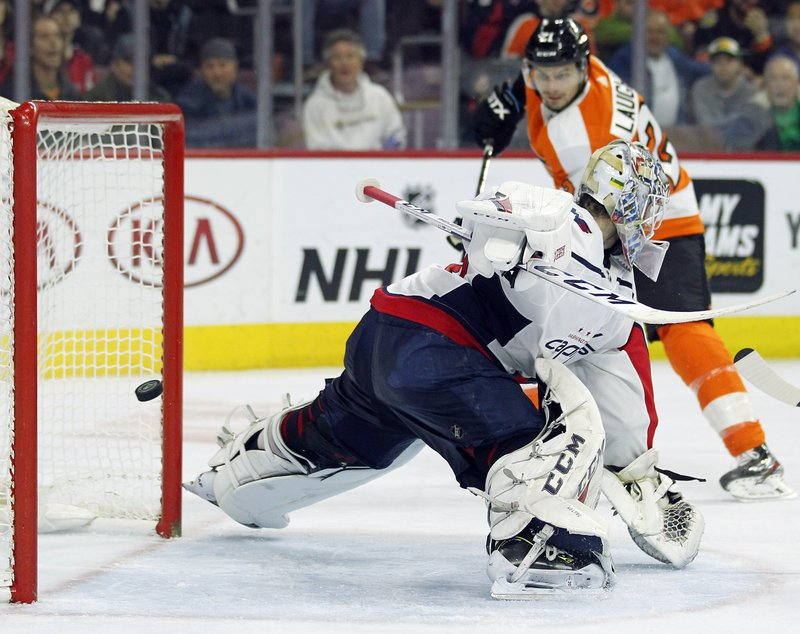 Washington Capitals' Braden Holtby fails to stop the shot as Philadelphia Flyers' Scott Laughton, rear, scores during the second period of an NHL hockey game Thursday, March 14, 2019, in Philadelphia. (AP Photo/Tom Mihalek)