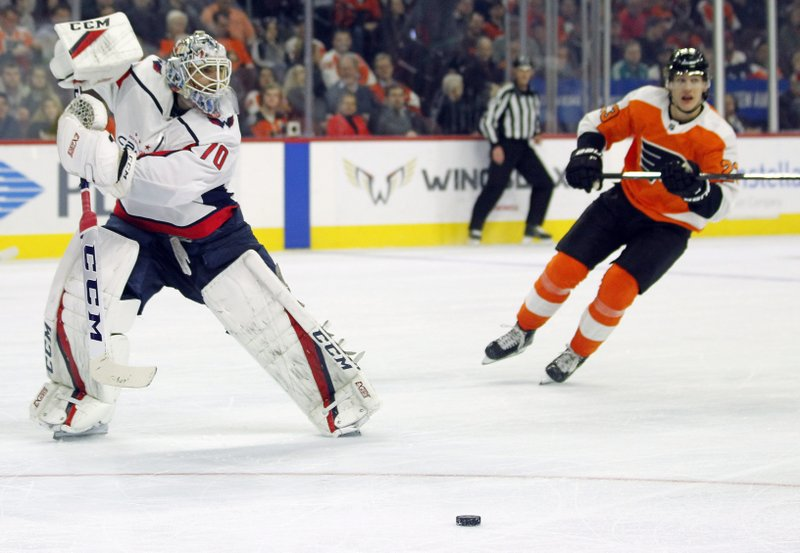 Washington Capitals goalie Braden Holtby is out of the crease as he directs the puck away from an approaching Philadelphia Flyers' Oskar Lindblom during the second period of an NHL hockey game Thursday, March 14, 2019, in Philadelphia. (AP Photo/Tom Mihalek)