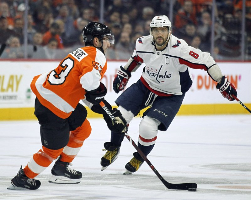 Philadelphia Flyers' Shayne Gostisbehere heads up ice as Washington Capitals' Alex Ovechkin advances on him during the third period of an NHL hockey game Thursday, March 14, 2019, in Philadelphia. (AP Photo/Tom Mihalek)