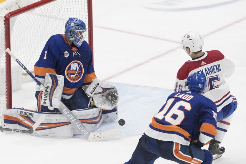 New York Islanders goaltender Thomas Greiiss, left, makes a save against Montreal Canadiens center Jesperi Kotkaniemi, upper right, during the third period of an NHL hockey game, Thursday, March 14, 2019, in Uniondale, N. (AP Photo/Mary Altaffer)
