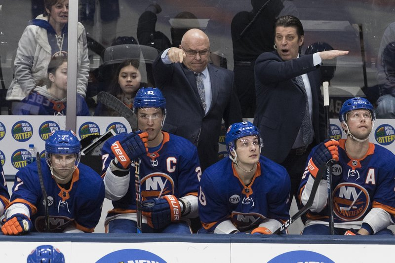 New York Islanders head coach Barry Trotz, back left, gestures during the third period of an NHL hockey game against the Montreal Canadiens, Thursday, March 14, 2019, in Uniondale, N. (AP Photo/Mary Altaffer)