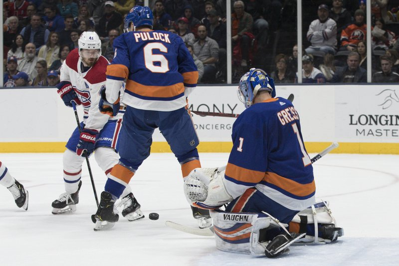 New York Islanders goaltender Thomas Greiss (1) and defenseman Ryan Pulock (6) make a save against Montreal Canadiens left wing Paul Byron (41) during the first period of an NHL hockey game, Thursday, March 14, 2019, in Uniondale, N. (AP Photo/Mary Altaffer)