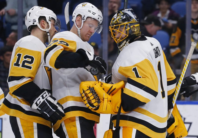 Pittsburgh Penguins forward Patric Hornqvist (72) gives the game puck to goalie Casey DeSmith (1) after the team's NHL hockey game against the Buffalo Sabres on Thursday, March 14, 2019, in Buffalo, N. (AP Photo/Jeffrey T. Barnes)