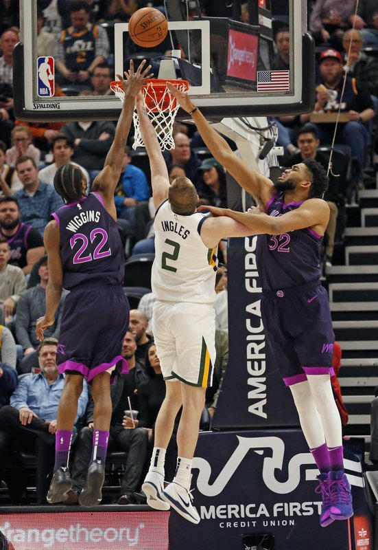 Minnesota Timberwolves' Andrew Wiggins (22) and Karl-Anthony Towns (32) defend against Utah Jazz forward Joe Ingles (2) in the first half during an NBA basketball game Thursday, March 14, 2019, in Salt Lake City. (AP Photo/Rick Bowmer)
